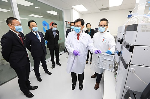Deputy Prime Minister Heng views the mass spectrometer, which detects and measures multiple test compounds in a single sample with greater accuracy, at the Centre.